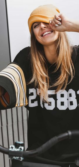 girl-in-hockey-jersey-style-with-street-bicycle-PEKUWLK-scaled.jpg