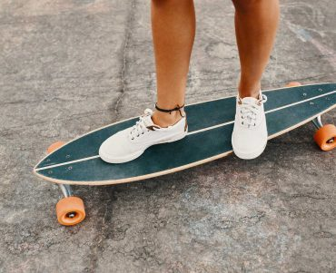 woman-in-sneakers-riding-skateboard-outdoor-on-asp-KXD8CUS.jpg
